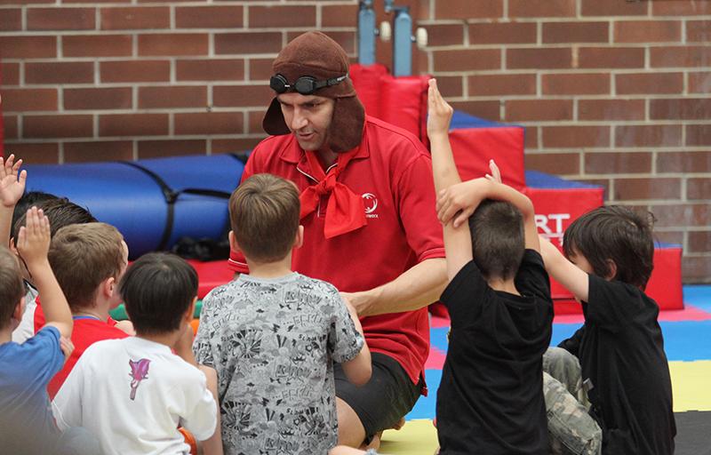 Fitnessworx facilitator dressed as a skylander instructing group of kids on participating in skylanders program