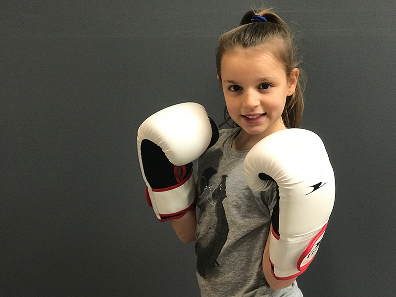 Girl wearing white boxing gloves and smiling at camera during bootcamp program