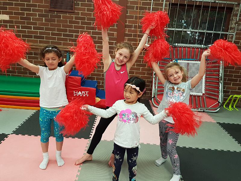 Four kids holding red pom poms overhead during kinder Dance n Movement school holiday program