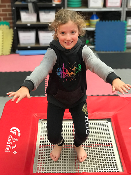 Girl bouncing on red mini tramp during cheerleading party