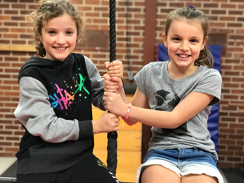 Two girls sitting on double static trapeze and holding middle rope during kids circus workshop school holiday program