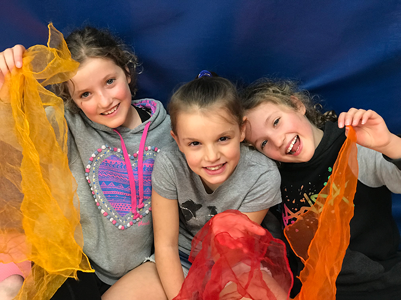 Three girls smiling and holding yellow, red and orange juggling scarves during custom made mobile party