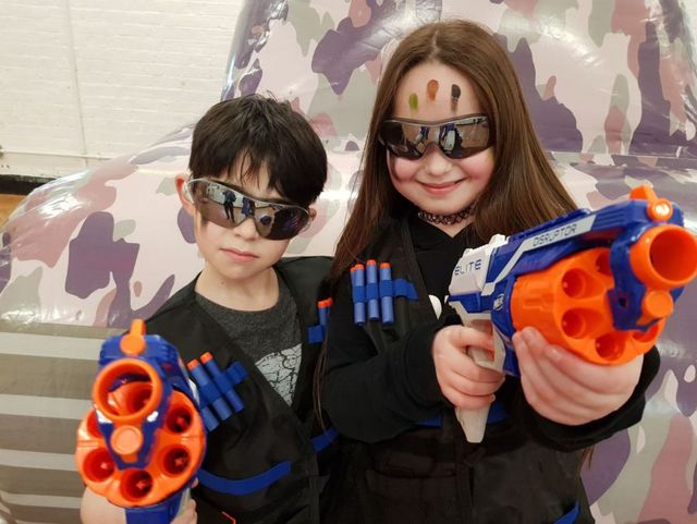 Boy and girl wearing sunglasses and pointing nerf guns at camera during nerf gun bootcamp program
