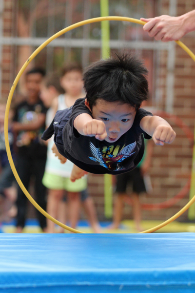 Small boy diving through yellow hoop as if he's 'flying' during Superhero Training Sports Coaching school holiday program