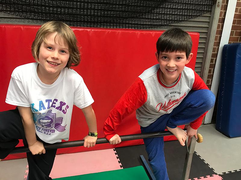 Two boys balancing on metal bar during parkour school holiday program