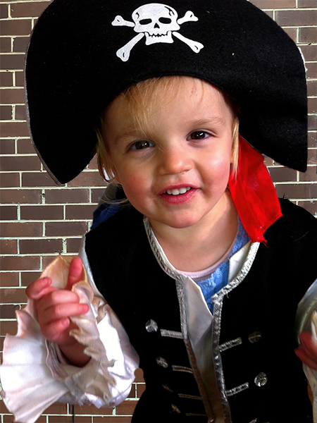 Young girl dressed in black pirate costume including hat with skull and crossbones during pirate party