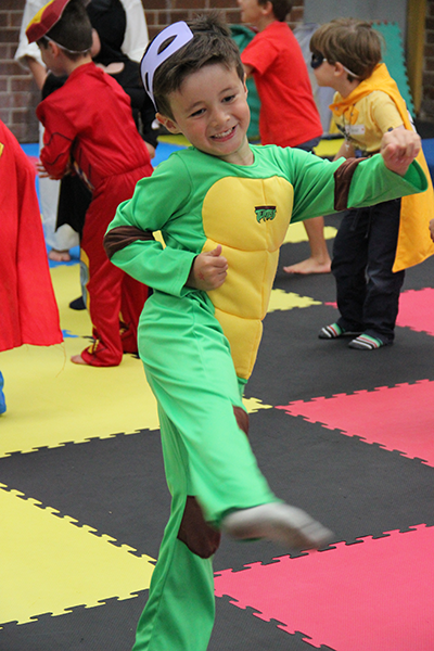Boy smiling and standing on one leg dressed as a ninja turtle during super hero training party