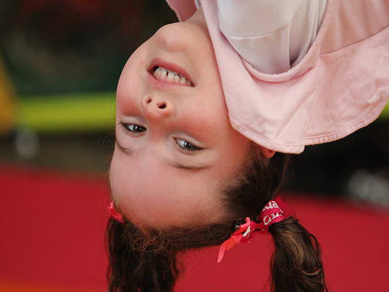 Girl hanging up-side-down during kinder circus school holiday programs