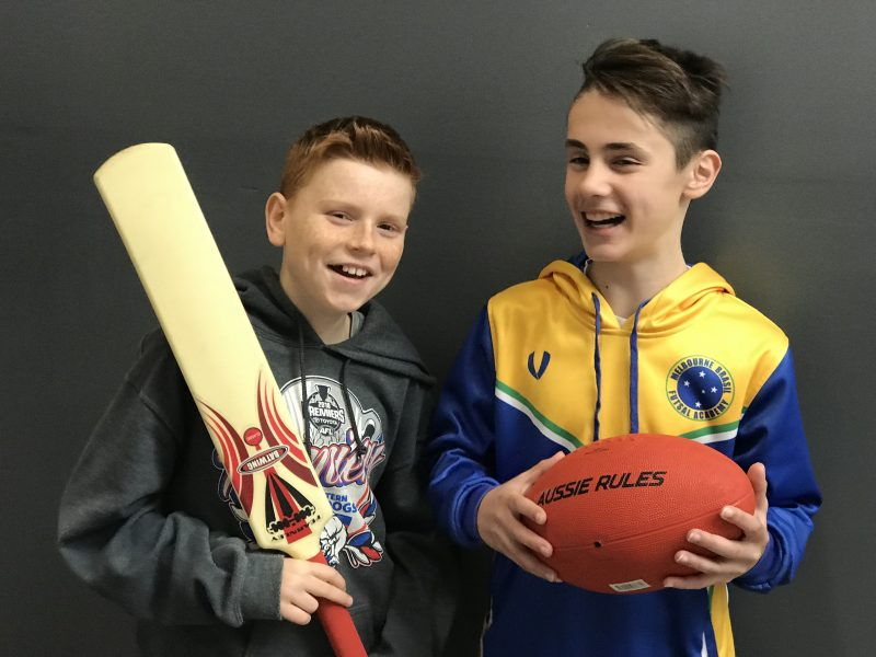 Boy holding cricket bat and boy holding red football during best tabloid sports parties Melbourne