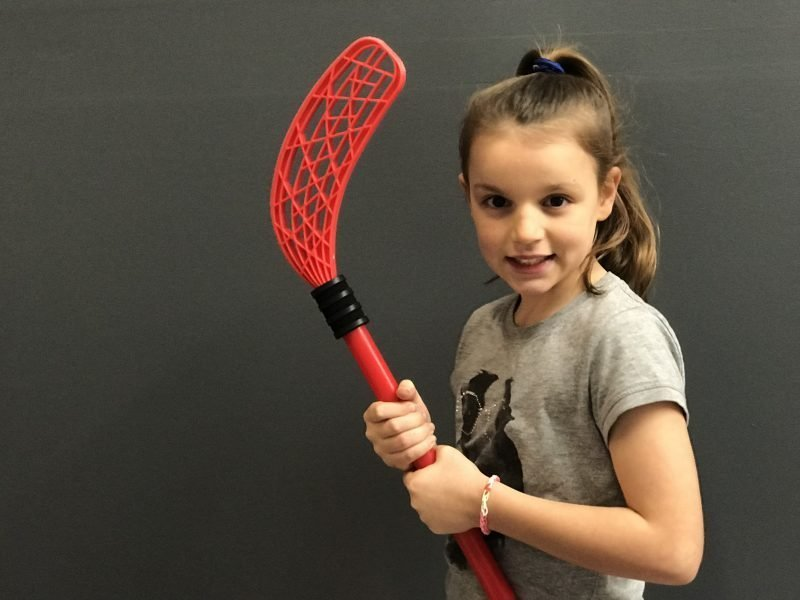 Girl holding red hockey stick and smiling during mini olympics program