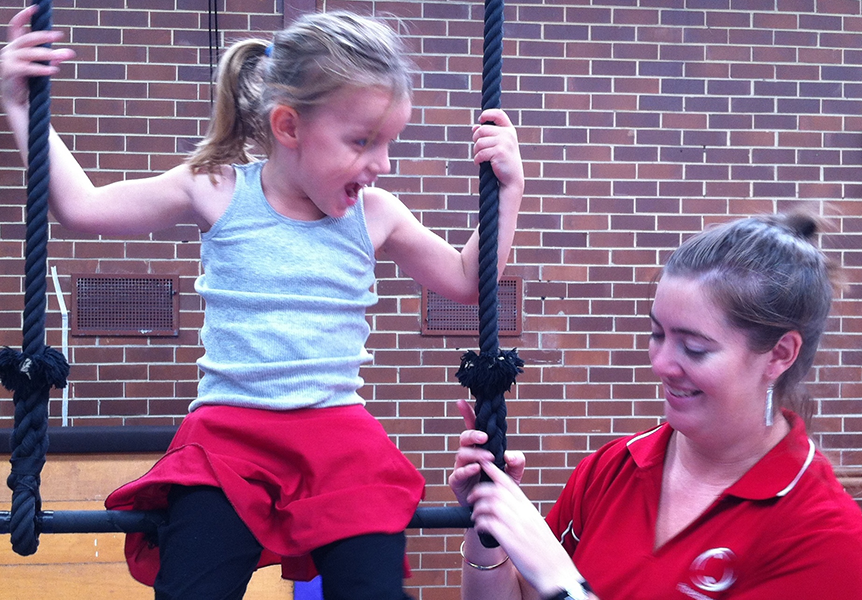 Young girl sitting on static trapeze and looking at Fitnessworx facilitator who is teaching her circus skills