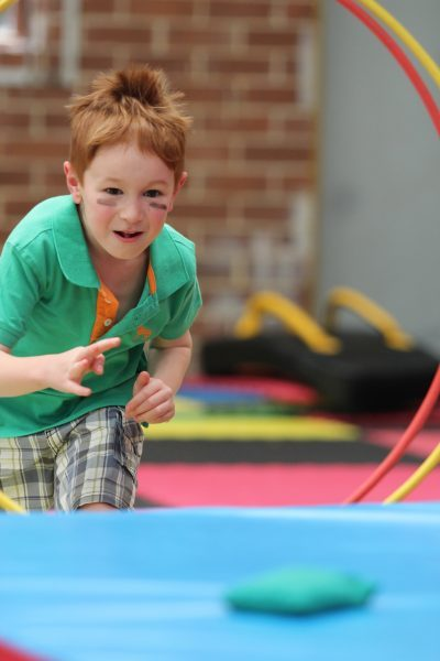 Boy with black stripes on cheeks about to dive through a hoop during a ninja warrior after school program