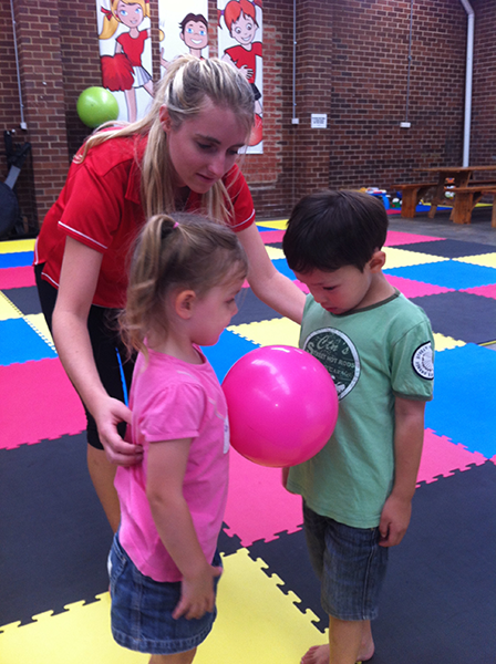 Girl and boy holding pink ball between them while female Fitnessworx facilitator teaches ball skills during Ball Sports Coaching Clinics kinder school holiday program