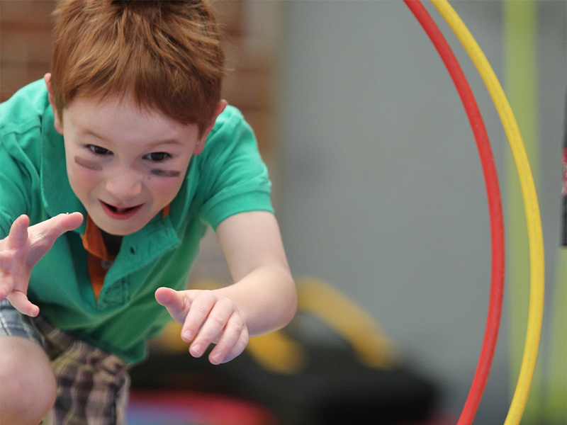 Boy with black stripes on his cheeks about to dive through a hoop during ninja warrior school holiday programs