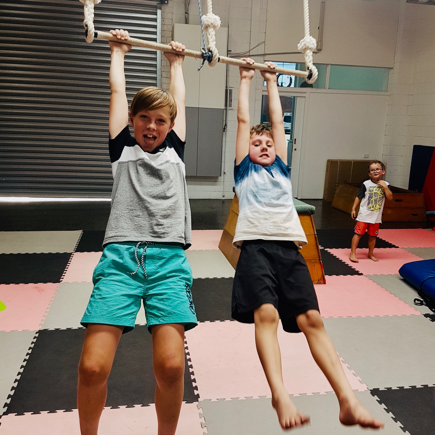 Two boys swinging on static trapeze during school holiday programs